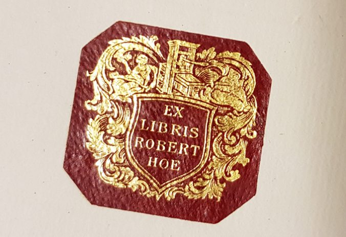 robert hoes exlibris, en liten etikett i rött skinn med en guldpressad vapenskäld i vilken står texten Ex libris Robert Hoe
