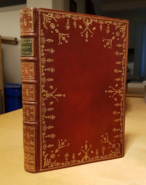 en röd bok stående på högkant, vilket visar guldtryckt dekor utmed pärmens kanter samt utmed hela ryggen
