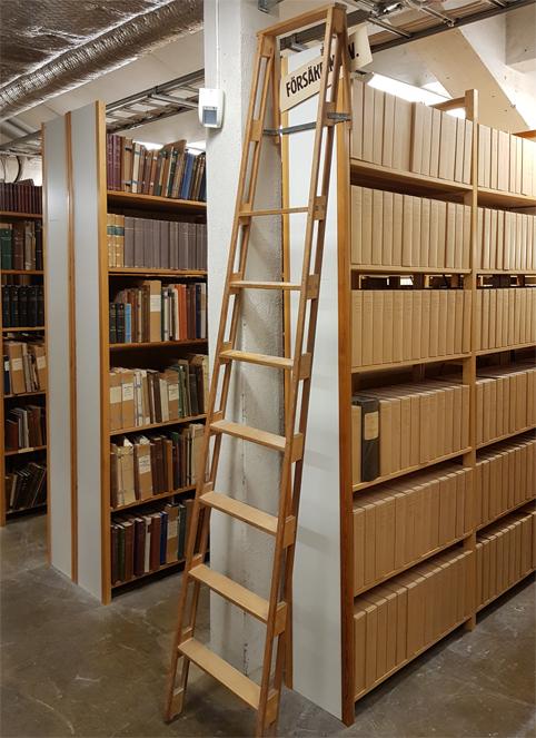 en stege står lutad mot gaveln på en rad med bokhyllor, på gaveln sitter en skylt med texten Försäkringsv.