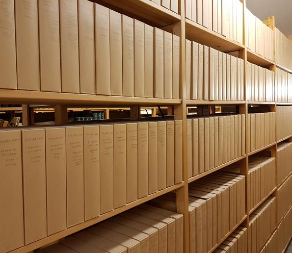 I bilden syns 18 hyllplan med identiska bruna papperskapslar med handskriven text på ryggarna, ordet Försäkr-väsen står överst på varje kapsel