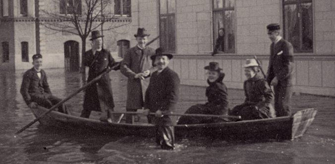 män och kvinnor i en stor roddbåt