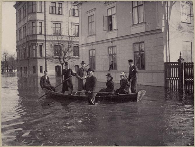 två kvinnor och fyra män i en stor roddbåt på vattnet på Skolgatan i Uppsala. Vattnet når en bra bit upp på huskropparna.