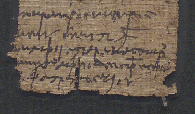 detalj av ett papyrusfragment med trasiga kanster, på bladet grekisk text med textbortfall i sidorna