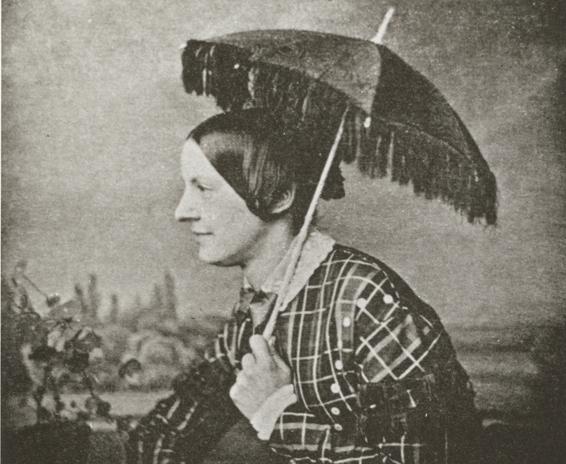 En ung dam i profil hållande ett parasoll över sitt huvud, iförd rutig klännning