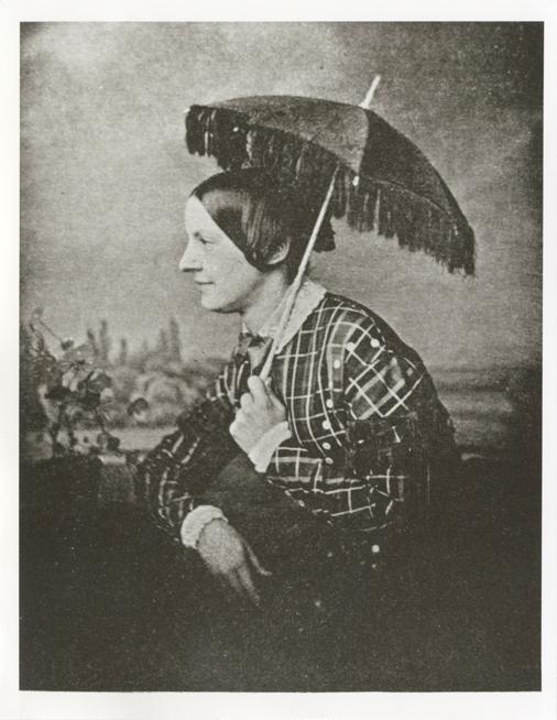 Jenny Lind sittande i profil, hållande ett svart parasoll över sitt  huvud och iförd en rutig klänning med vit krage och vita knappar