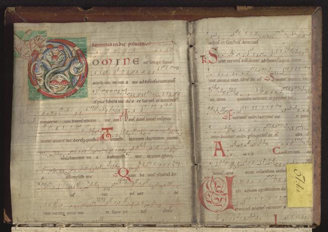Handskrivna noter med en inledande initial i grönt, blått och rött med ett lejon i kanten.