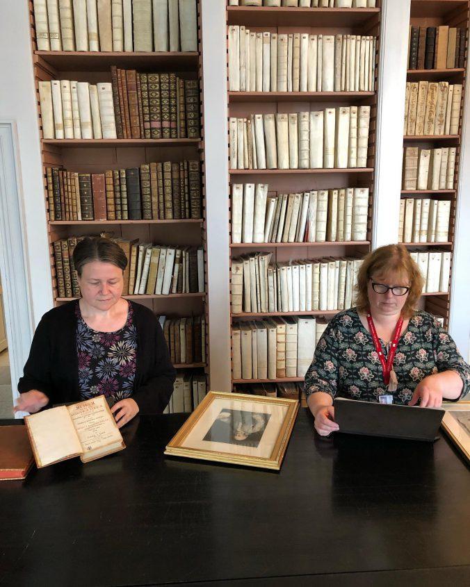 två kvinnor står lutade över uppsalgna böcker och bilder vid ett bord, i bakgrunden bokhyllor fulla av gamla böcker