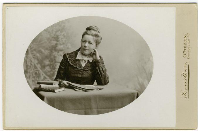 en ung selma lagerlöf sitter vid ett bord med en uppslagen bok framför sig